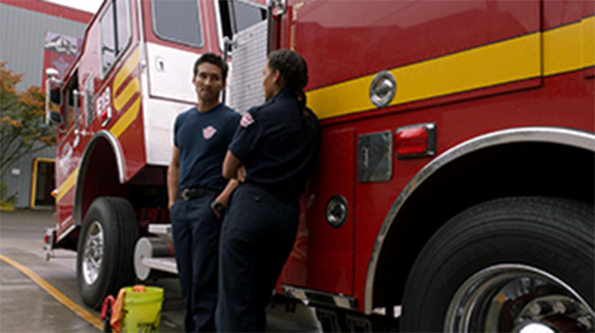 Two uniformed firefighters standing in front of a fire truck