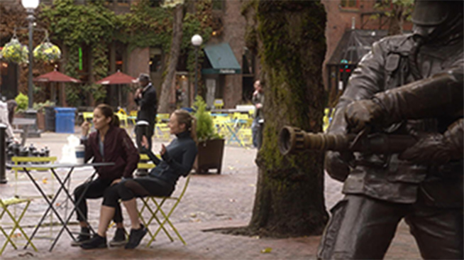 Two women talking and sitting at a table in Seattle's Occidental Park, near the Memorial to Fallen Firefighters.