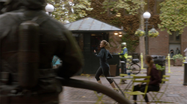 A woman in Seattle's Occidental Park, running past the Memorial to Fallen Firefighters.