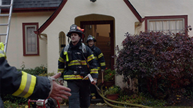 Firefighters coming out of a cream house with dark red trim. There is a ladder propped against the roof and the firefighters carry hoses.