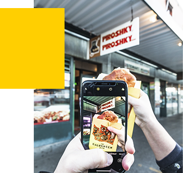 A person using their camera to take a photo of a piroshky in front of the Piroshky Piroshky storefront