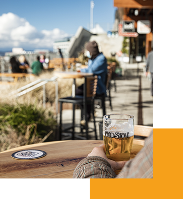 A person holding a glass of beer while sitting on the outdoor patio at Old Stove Brewing