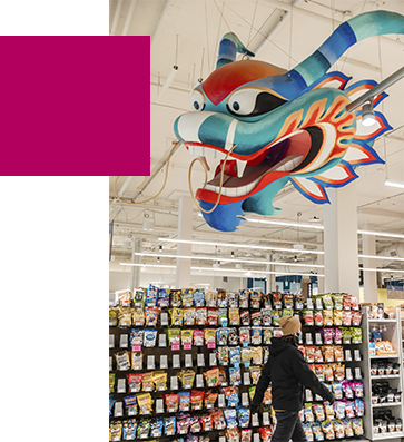 A person walking under a paper dragon in front of displayed snacks in Uwajamaya